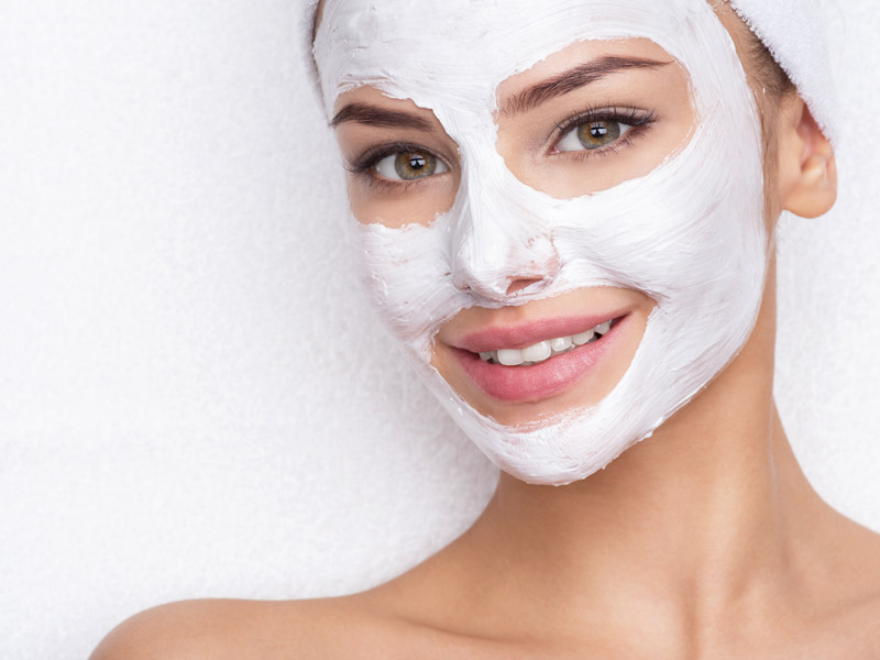smiling-woman-in-spa-salon-with-cosmetic-mask-on-f-6EGH9B3.jpg