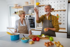 Senior couple having fun, cooking together in home kitchen