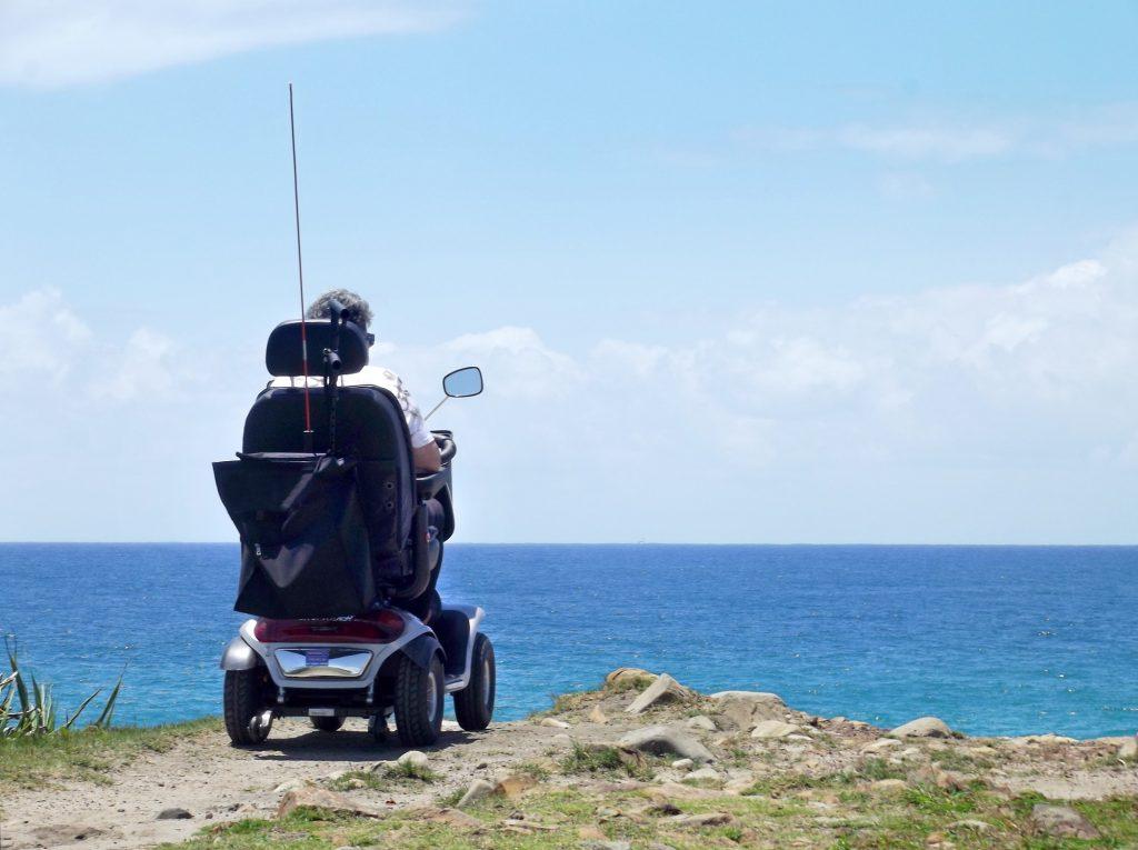 Woman in an electric wheelchair at the beach